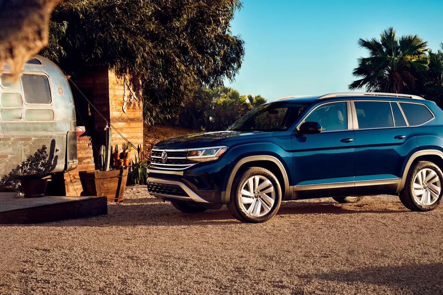 Side exterior view of the 2021 Volkswagen Atlas parked outside of a remote home beside a trailer